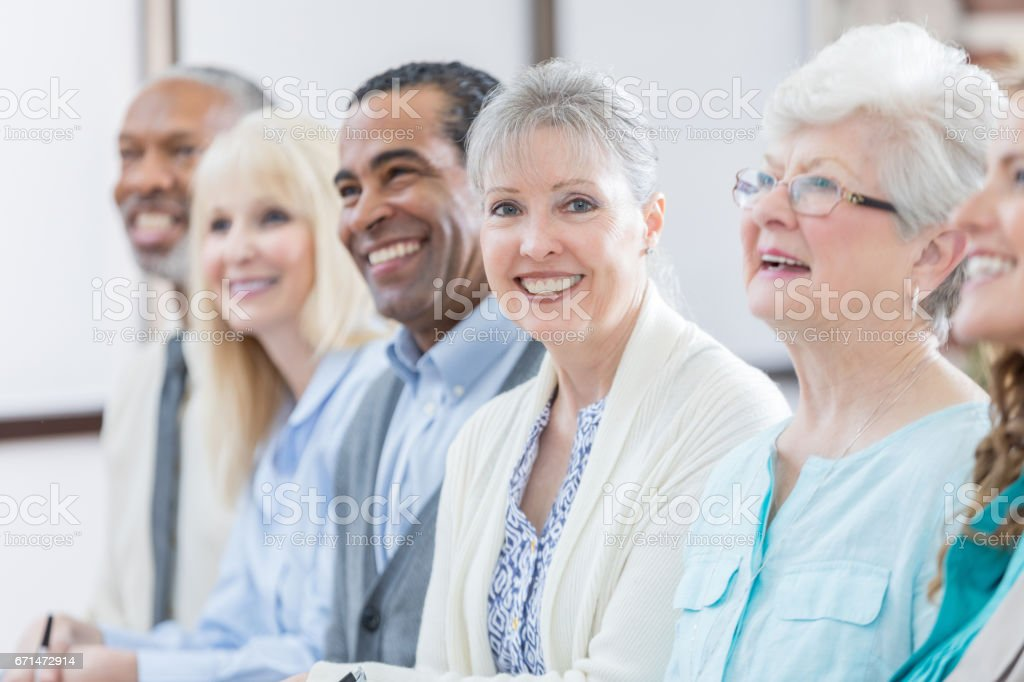 Cheerful senior women enjoys continuing education seminar stock photo