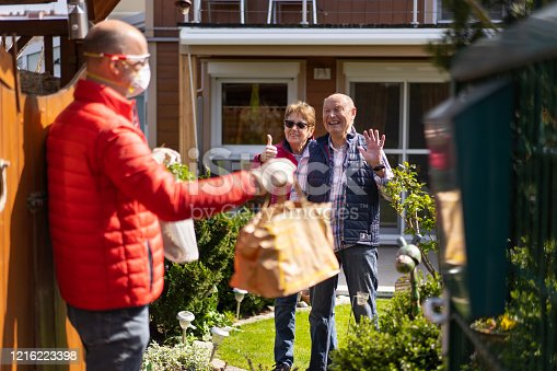 contactless home delivery food supply at open garden fence door for very happy thankful senior couple waiting in their garden, man with paper bags blurred in foreground