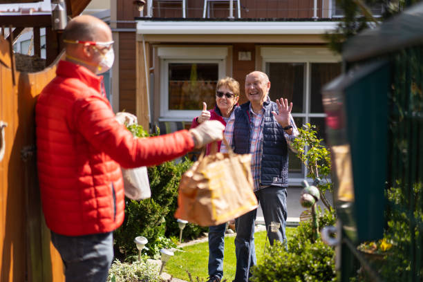 cheerful seniors happy and grateful for food delivery from helpful neighbor during covid-19 stock photo