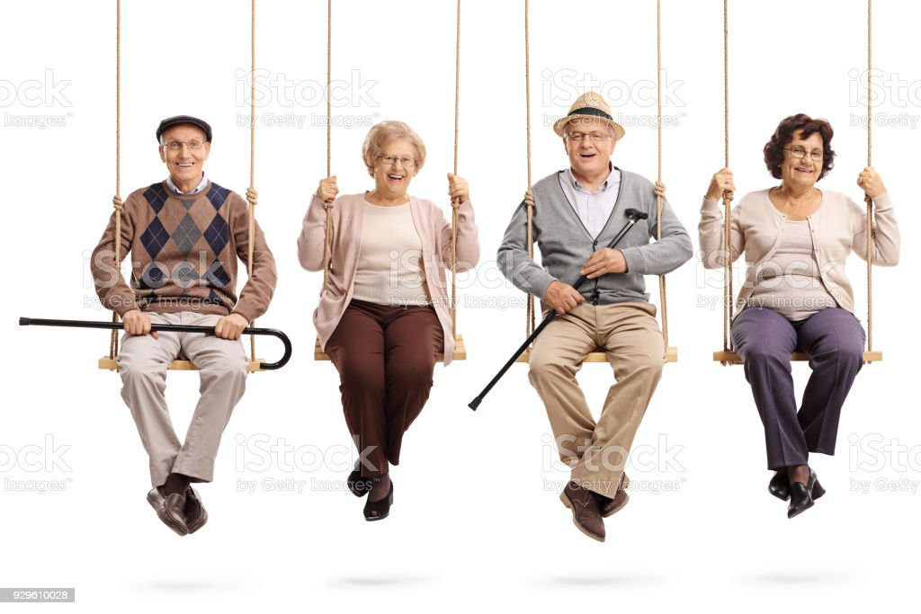 Cheerful seniors sitting on wooden swings and looking at the camera - foto stock