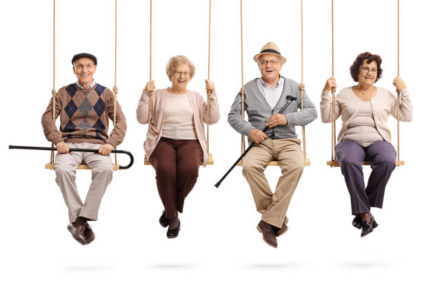 Cheerful seniors sitting on wooden swings and looking at the camera Cheerful seniors sitting on wooden swings and looking at the camera isolated on white background four people stock pictures, royalty-free photos & images