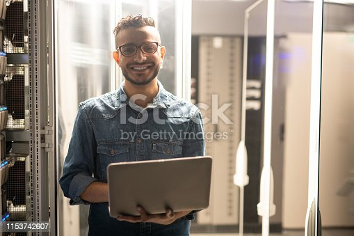 istock Cheerful server engineer in datacenter room 1153742607