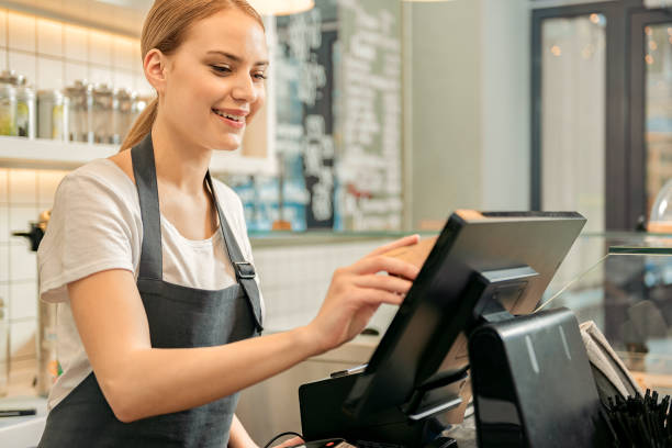 Cheerful shop assistant using digital device for payment Joyful young saleswoman is receiving money from customer. She is holding credit card near screen and smiling sales clerk stock pictures, royalty-free photos & images