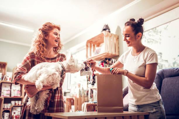 快樂的購物助理給狗聞一些食物 - small business saturday 個照片及圖片檔