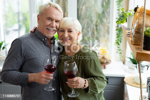 Cuddling and keeping glasses. Cheerful loving smiling beautiful beaming glowing contended nice-appealing aged silver-haired spouses in elegant clothing cuddling and keeping glasses with red wine.