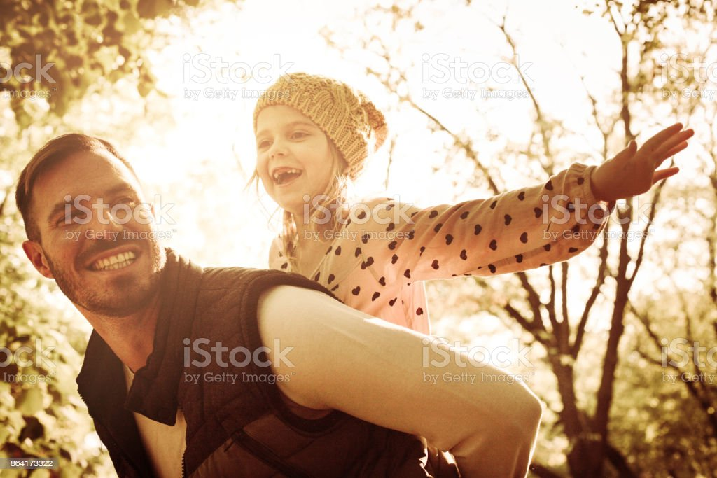 Cheerful single father carrying his daughter on piggyback and enjoying in park. royalty-free stock photo