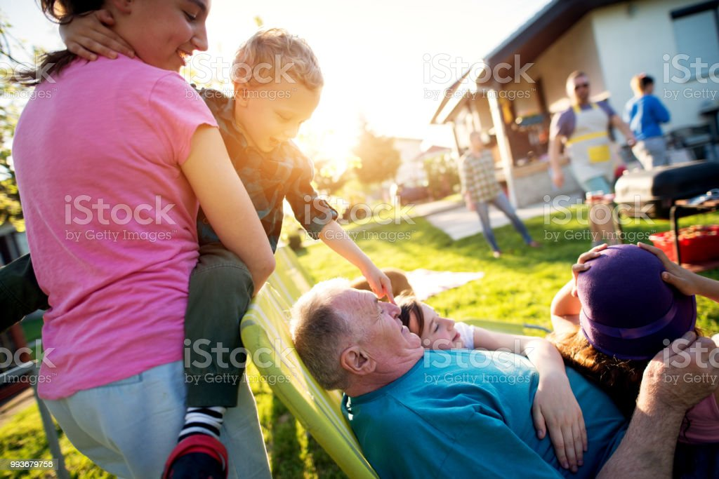 Cheerful sister is holding her little toddler brother as he boops grandfather nose who is holding rest of the grandchildren while rest of the family is busy grilling. stock photo