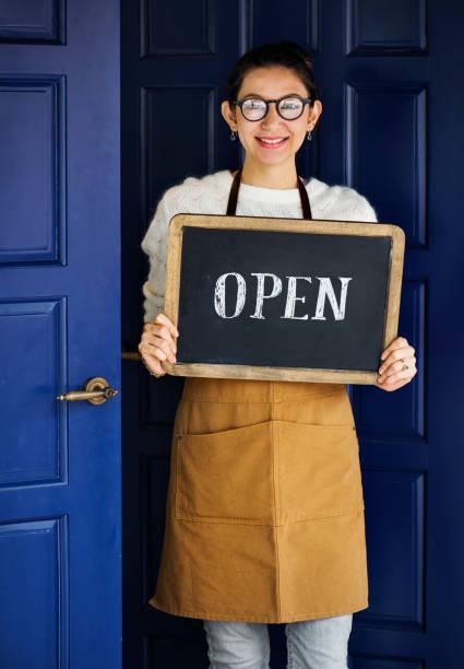 Dueño de un negocio pequeño alegre con señal abierta - foto de stock