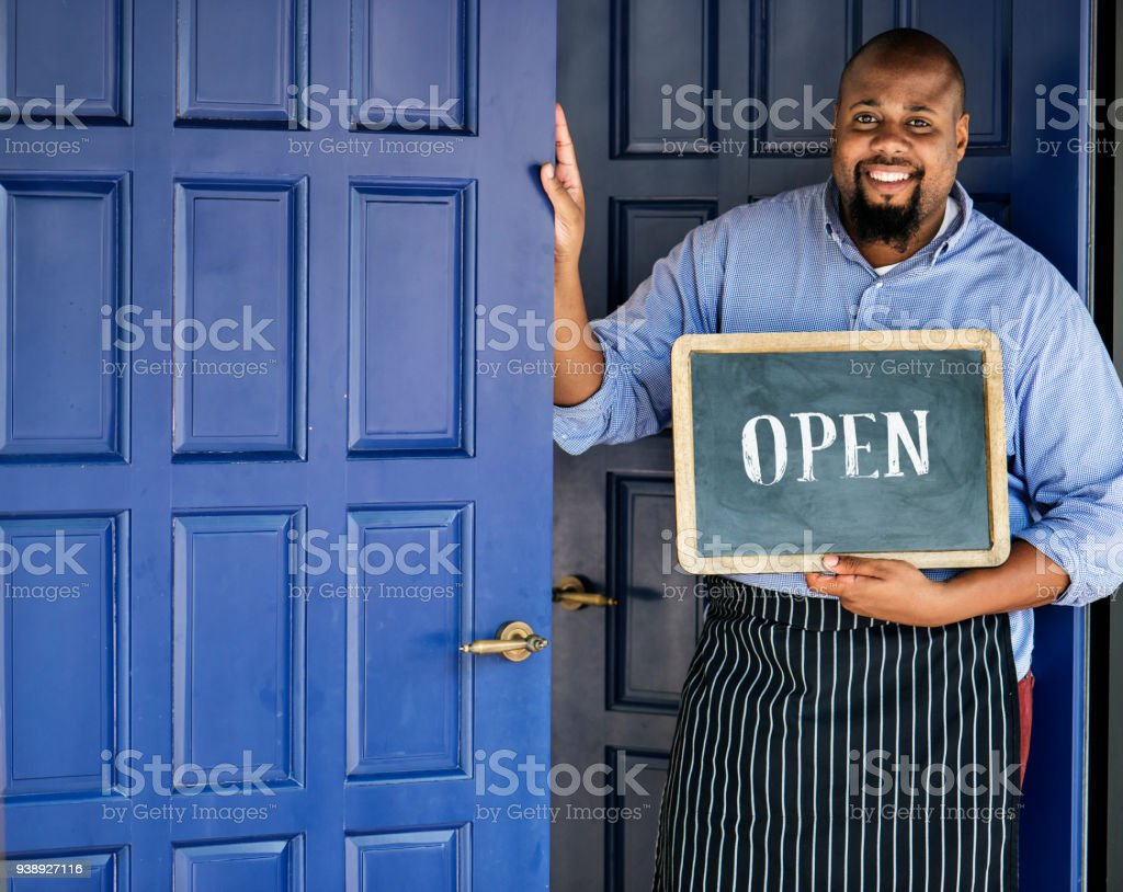 A cheerful small business owner with open sign stock photo