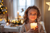 Front view of cheerful small girl standing indoors at Christmas, holding candle.