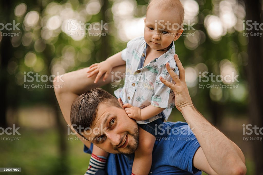 Cheerful small son on shoulders at the daddy in summer royalty-free stock photo