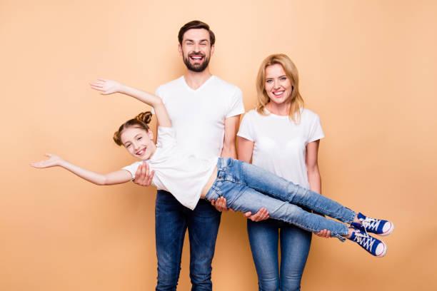 sonrisa alegre barbudo padre y carring rubia madre feliz su descendencia hija pequeña en brazos sobre fondo beige - moda playera fotografías e imágenes de stock