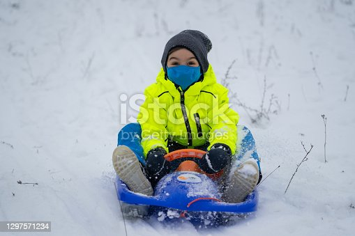 happy smiling behind the mask 6 years old boy in winter clothes sledging on snowy hill with his bobsled in times of corona virus