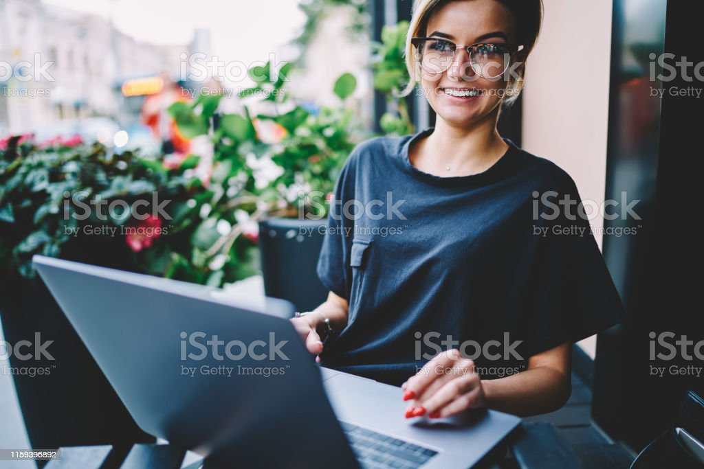 Cheerful smiling hipster girl 20s chatting with friends on computer...