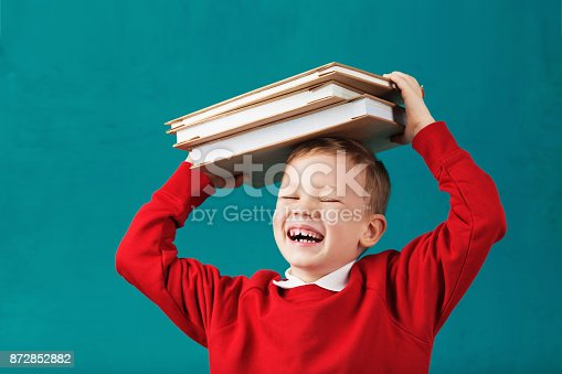 istock Cheerful smiling little school boy in red sweatshirt holding big heavy books on his head against turquoise wall. Looking at camera. School concept 872852882