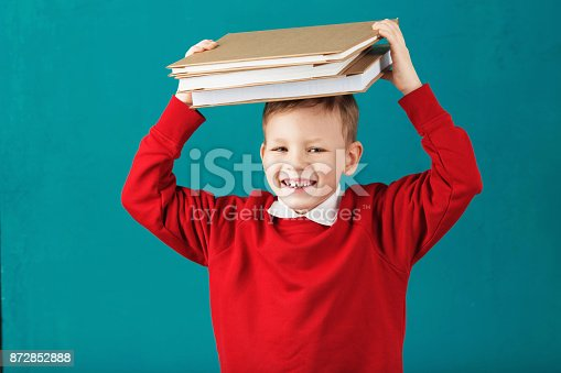 istock Cheerful smiling little school boy in red sweatshirt holding big heavy books on his head against turquoise wall. Looking at camera. School concept 872852888