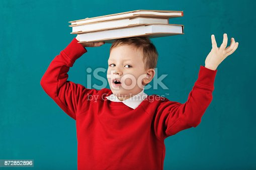 istock Cheerful smiling little school boy in red sweatshirt holding big heavy books on his head against turquoise wall. Looking at camera. School concept 872852896