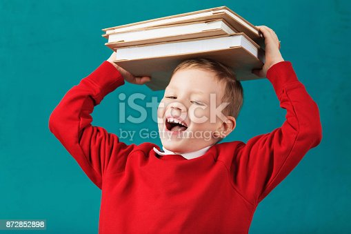 istock Cheerful smiling little school boy in red sweatshirt holding big heavy books on his head against turquoise wall. Looking at camera. School concept 872852898