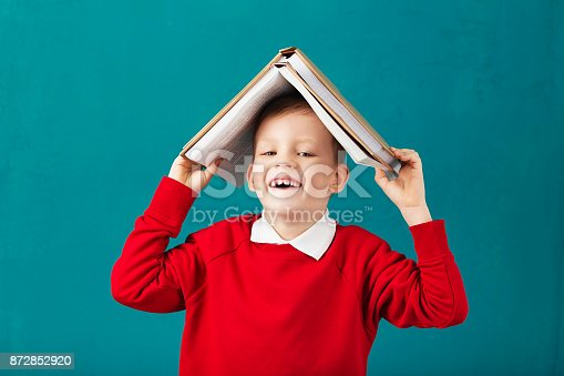 istock Cheerful smiling little school boy in red sweatshirt holding big heavy books on his head against turquoise wall. Looking at camera. School concept 872852920