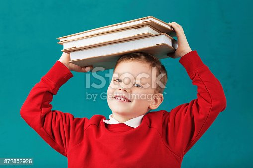 istock Cheerful smiling little school boy in red sweatshirt holding big heavy books on his head against turquoise wall. Looking at camera. School concept 872852926