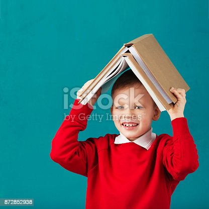 istock Cheerful smiling little school boy in red sweatshirt holding big heavy books on his head against turquoise wall. Looking at camera. School concept 872852938