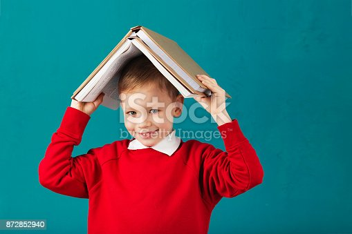 istock Cheerful smiling little school boy in red sweatshirt holding big heavy books on his head against turquoise wall. Looking at camera. School concept 872852940