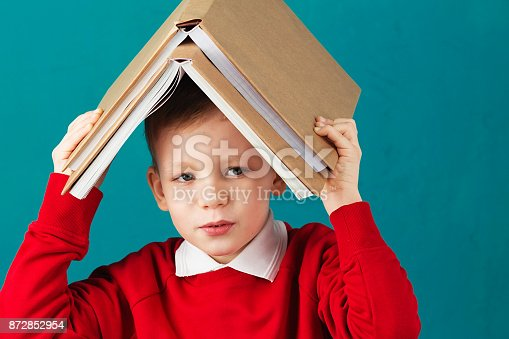 istock Cheerful smiling little school boy in red sweatshirt holding big heavy books on his head against turquoise wall. Looking at camera. School concept 872852954