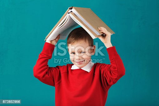 istock Cheerful smiling little school boy in red sweatshirt holding big heavy books on his head against turquoise wall. Looking at camera. School concept 872852956