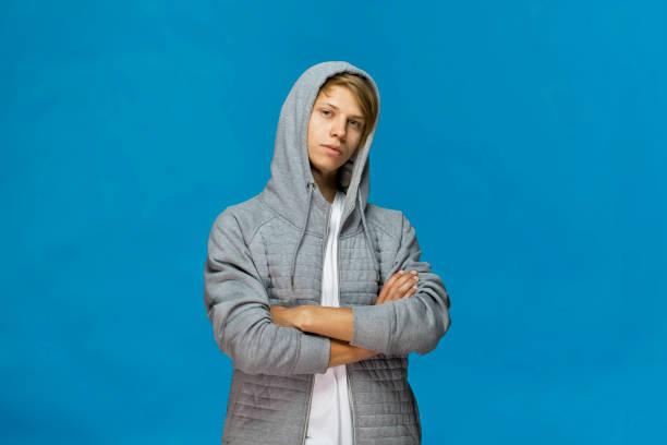 Fröhlich lächelnd Teenager in graue Bluse mit Kapuze und verschränkten Armen vor blauem Hintergrund Studioaufnahme, isoliert – Foto