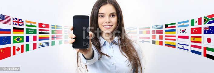 istock cheerful smiling woman showing blank smartphone screen, with international flags in background 679449988