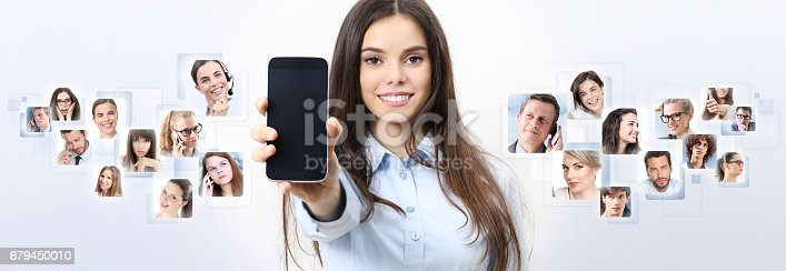 istock cheerful smiling woman showing blank smartphone screen, with person in background. social network concept 679450010