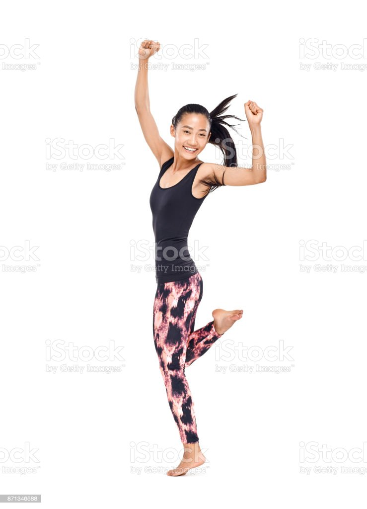 Cheerful smiling young Asian woman in sportswear dancing isolated stock photo