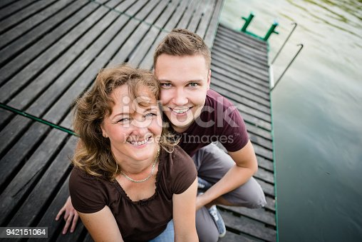 Mother with her adult son sitting on a wooden pier near forest lake.