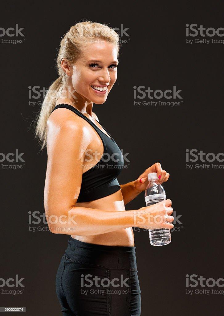 Cheerful sports woman holding water bottle royaltyfri bildbanksbilder