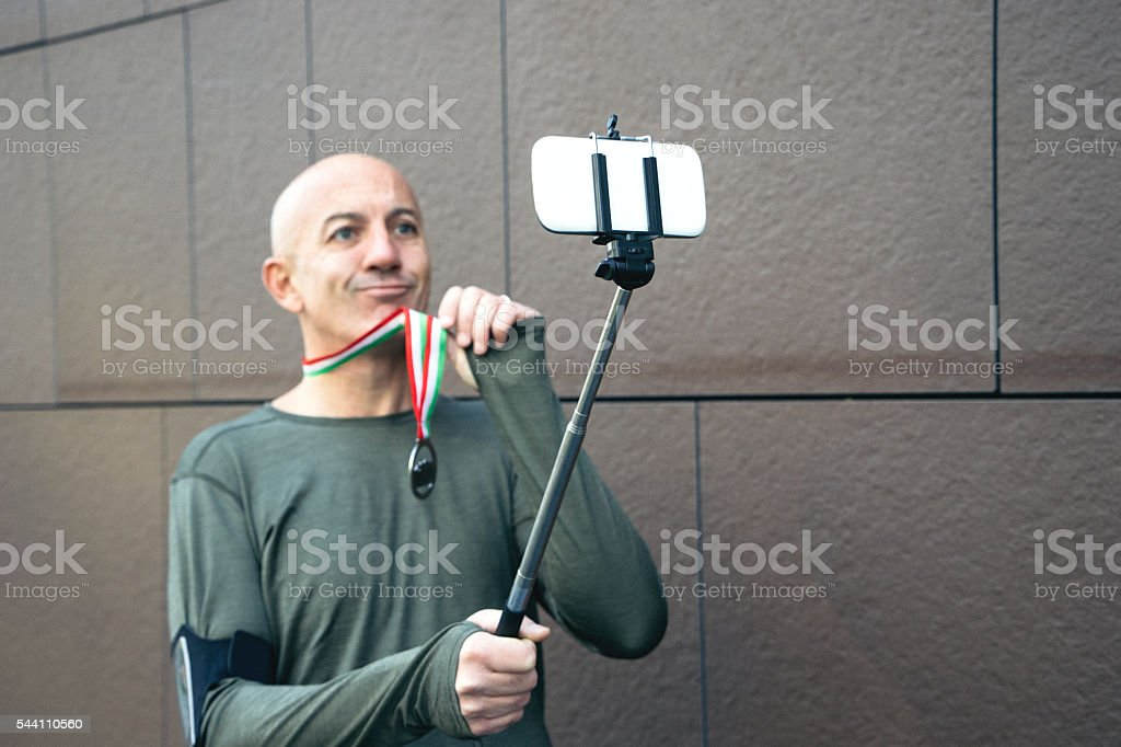 Cheerful Sportsman Taking Selfie With His Victory Medal stock photo