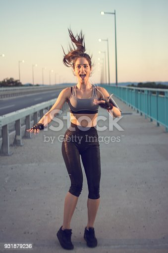 istock Cheerful sporty girl jumping outdoors. Young sportswoman celebrating successful training on the street. 931879236
