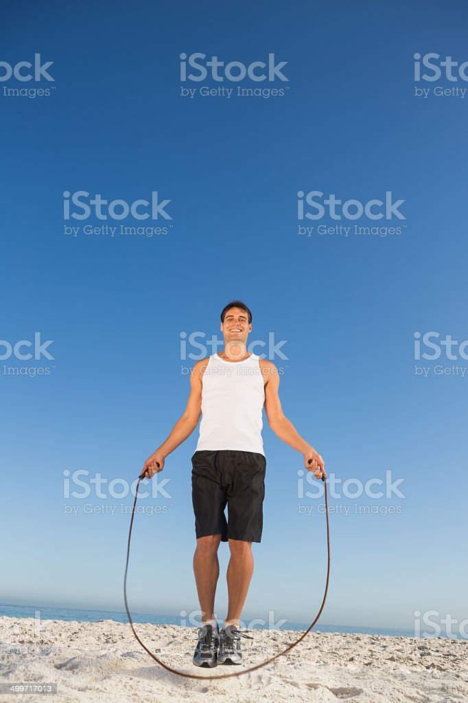 Cheerful sporty man jumping rope stock photo