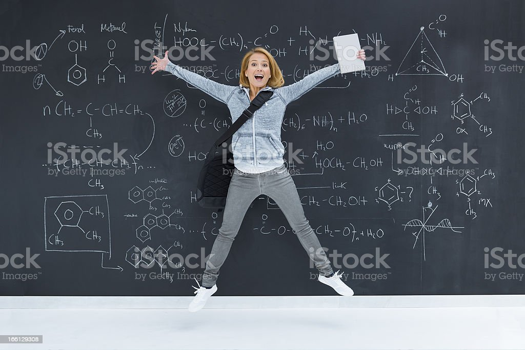 Cheerful student by blackboard stock photo