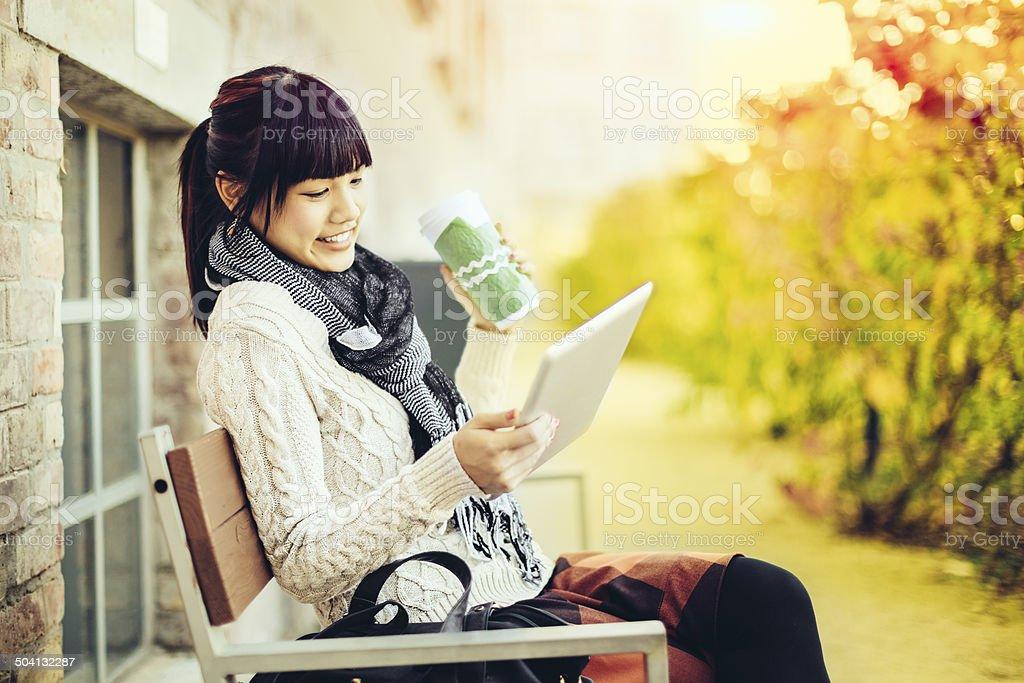 Cheerful student girl drinking coffee stock photo