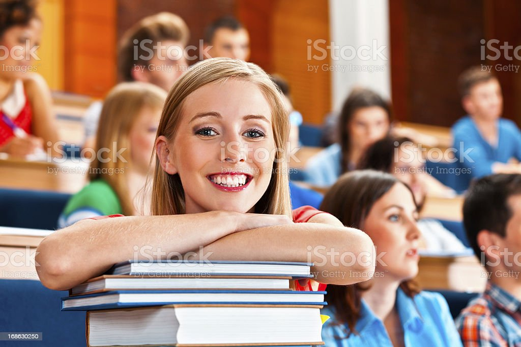 Cheerful student Large group of high school students sitting in the lecture hall. Focus on the beautiful young woman smiling at the camera. 20-24 Years Stock Photo