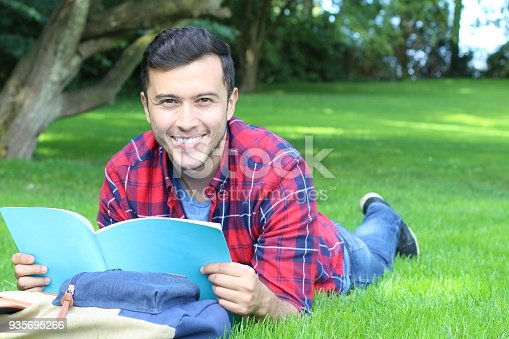 868483314 istock photo Cheerful student reading in the park 935695266