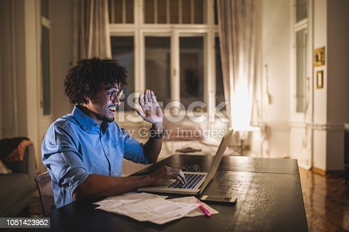 Young and determined black student studying at night at home, with a help of a laptop computer, and having a internet call.