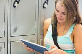 ロッカーの横にある彼女のタブレットを使用して陽気な学生
