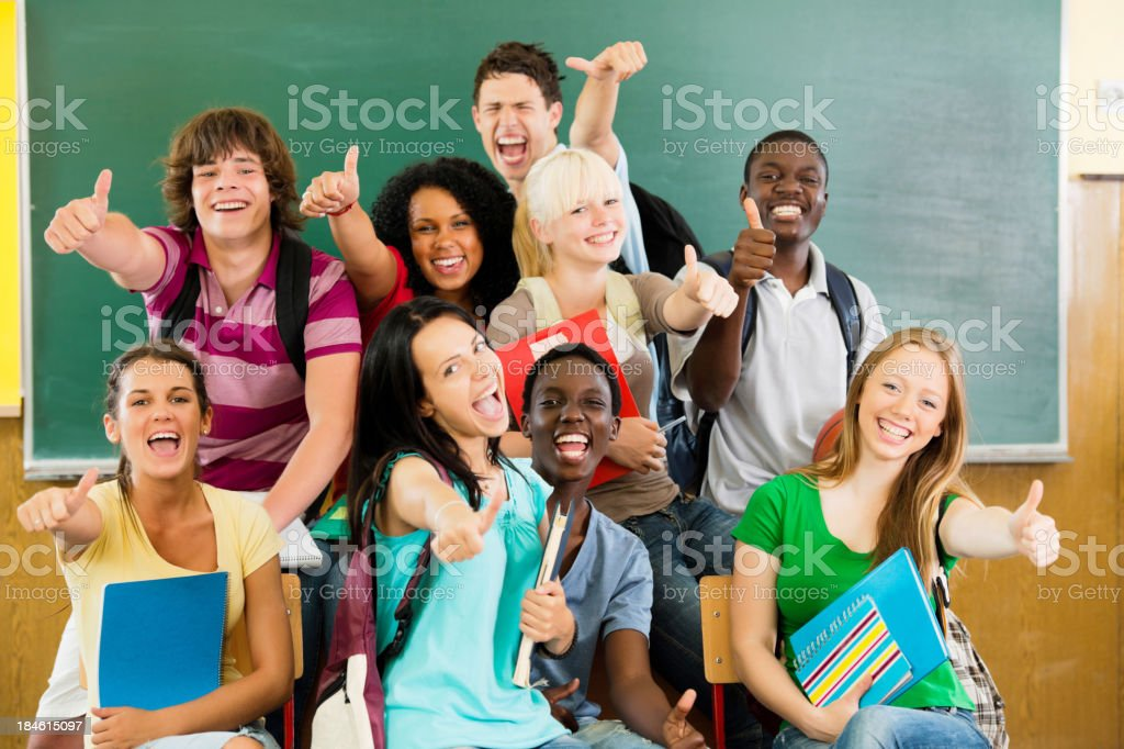 Cheerful students looking at the camera with their thumbs up. royalty-free stock photo
