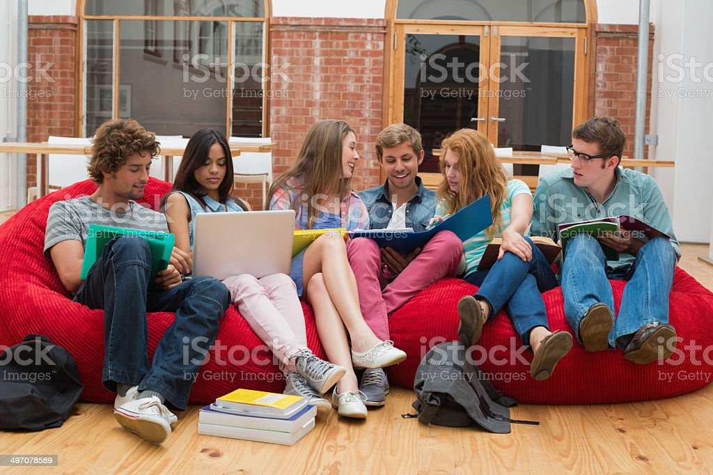 Cheerful students sitting on bean bags revising stock photo
