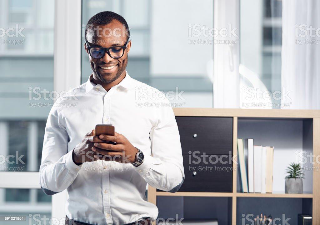 Cheerful stylish businessman is using his smartphone stock photo