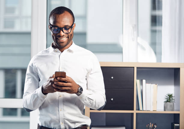 Cheerful stylish businessman is using his smartphone stock photo