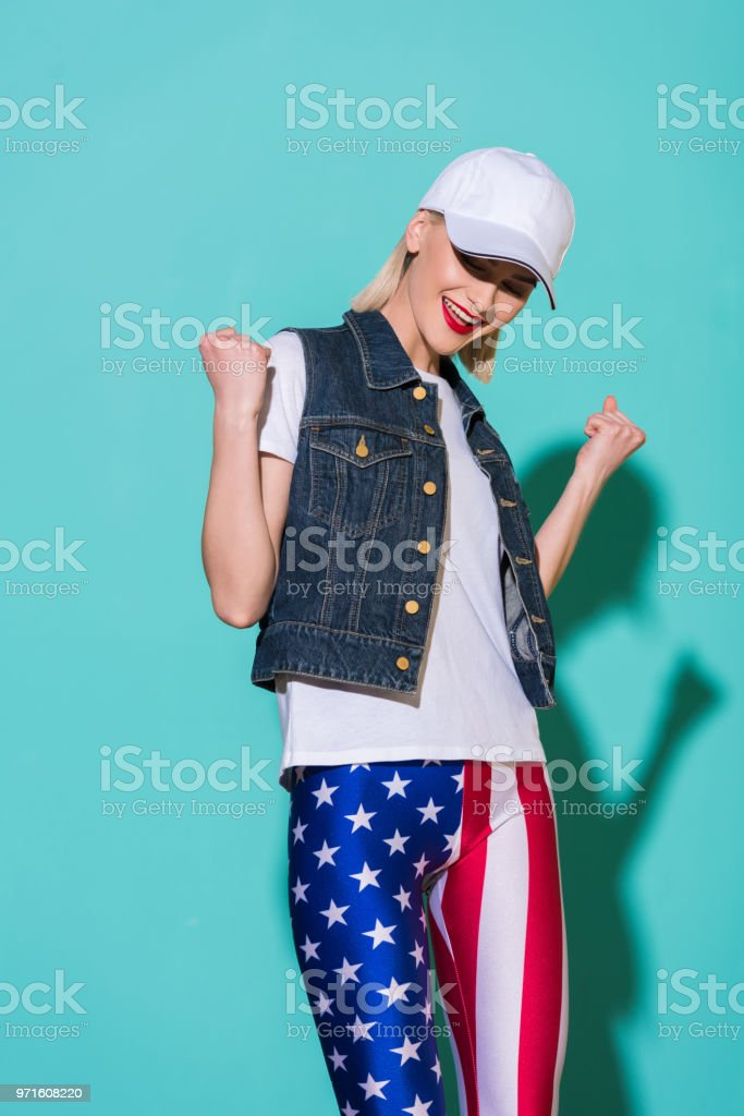 Cheerful Stylish Woman In Cap White Shirt Denim Jacket And Leggings