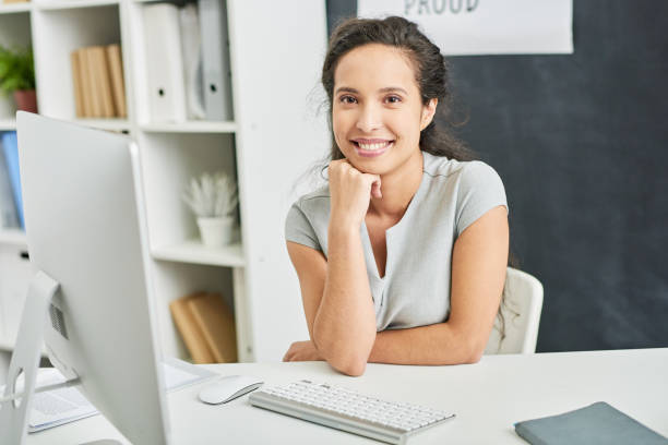 Cheerful successful female project manager Positive excited beautiful young mixed race businesswoman leaning head on hand while sitting at table with computer and looking at camera in office project manager stock pictures, royalty-free photos & images