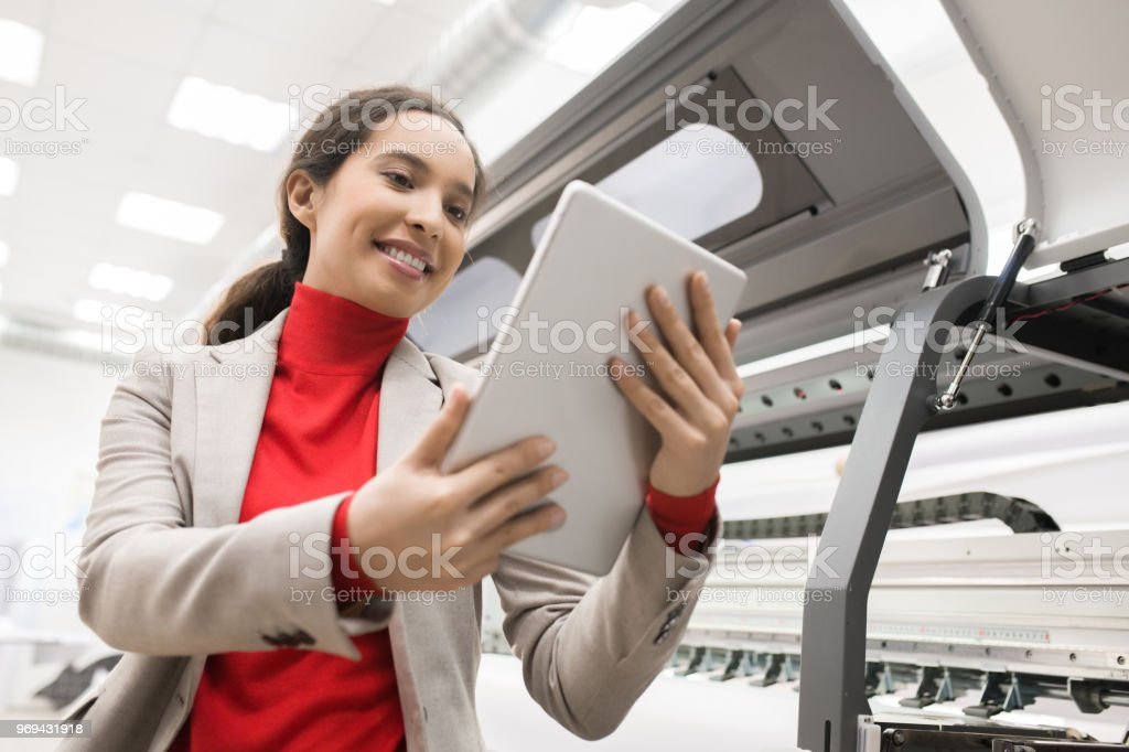 Cheerful successful mixed race female printing machine operator using tablet to manage large scale format printing machine in modern office stock photo